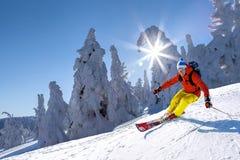 Sciatore che scia in discesa in alte montagne contro il cielo blu Fotografia Stock
