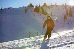 Sciatore che scia in discesa in alte montagne contro il tramonto Immagine Stock