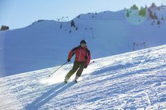 Sciatore che scia in discesa in alte montagne contro il tramonto Fotografie Stock Libere da Diritti