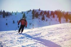 Sciatore che scia in discesa in alte montagne contro il tramonto Immagini Stock