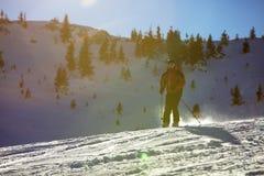 Sciatore che scia in discesa in alte montagne contro il tramonto Fotografia Stock