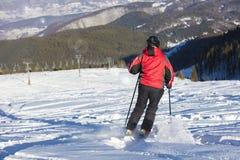 Sciatore che scia in discesa in alte montagne contro il tramonto Fotografie Stock