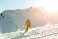 Sciatore che scia in discesa in alte montagne contro il tramonto Immagini Stock Libere da Diritti