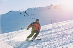 Sciatore che scia in discesa in alte montagne contro il tramonto Fotografia Stock Libera da Diritti