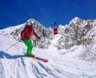 Sciatore che scia in discesa in alte montagne contro l'ascensore del cavo Immagine Stock