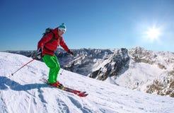 Sciatore che scia in discesa in alte montagne contro l'ascensore del cavo Fotografie Stock Libere da Diritti