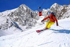 Sciatore che scia in discesa in alte montagne contro l'ascensore del cavo Fotografia Stock