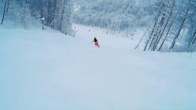 Sciatore che scia giù i pendii governati della montagna nella sera stock footage