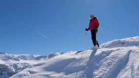 Sciatore del ritratto che sta su The Edge e che ammira il panorama delle montagne stock footage