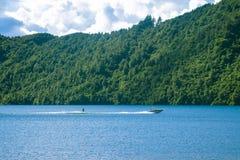 Sciatore dell'acqua sul lago con la barca Imbarco di risveglio della persona il giorno soleggiato fotografia stock libera da diritti
