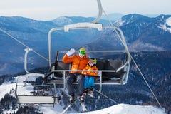 Sciatore dell'uomo con l'ascensore del bambino sulla sedia del ropeway Immagine Stock