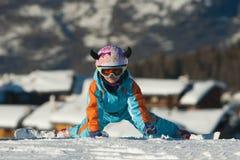 Sciatore della bambina sulle sue ginocchia Immagine Stock