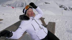 Sciatore della donna al riposo ed all'abbronzatura nelle montagne che si siedono sul banco archivi video