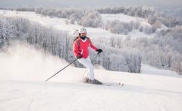Sciatore della donna che corre in discesa sulla pista della neve Immagini Stock