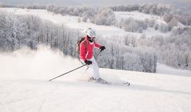 Sciatore della donna che corre in discesa sulla pista della neve Fotografia Stock Libera da Diritti