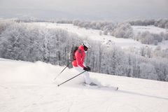 Sciatore della donna che corre in discesa sulla pista della neve Fotografie Stock