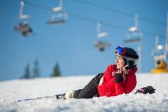 Sciatore della donna con lo sci alla località di soggiorno del winer nel giorno soleggiato Fotografia Stock Libera da Diritti