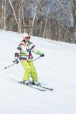 Sciatore della ragazza che scende il pendio il giorno soleggiato Fotografia Stock