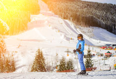Sciatore della ragazza contro i pendii dello sci e ski-lift su fondo Fotografia Stock Libera da Diritti