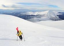 Sciatore di visita alpino che fa un'escursione in montagne di inverno Immagini Stock