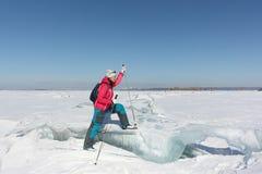 Sciatore felice della donna che fa un passo su una banchisa su un fiume congelato Immagine Stock