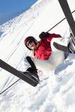 Sciatore femminile che si siede nella neve con dopo la caduta Fotografia Stock