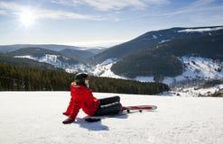Sciatore femminile che si trova sulla neve, alta montagna Fotografie Stock