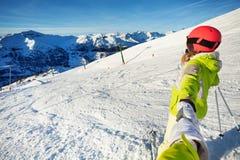 Sciatore femminile che tira uomo per sciare insieme Fotografie Stock
