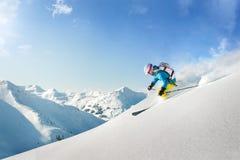 Sciatore femminile di freeride nelle montagne Immagine Stock