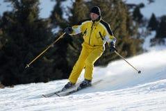 Sciatore giallo sul pendio del pattino Immagini Stock Libere da Diritti