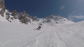 Sciatore maturo attivo che scia giù dai pendii di montagna nell'inverno sullo sci alpino video d archivio