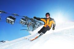 Sciatore in montagne, piste pronto e giorno pieno di sole Immagini Stock