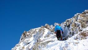 Sciatore remoto maschio che fa un'escursione ad un'alta sommità alpina in Svizzera lungo una cresta della neve e della roccia Fotografia Stock