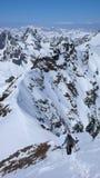Sciatore remoto maschio che fa un'escursione lungo una cresta stretta della neve con un grande paesaggio della montagna dietro lu fotografie stock