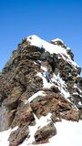 Sciatore remoto maschio che scala ad una sommità rocciosa esposta con i suoi sci attaccati al suo zaino immagine stock