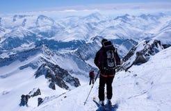 Sciatore remoto maschio che scia giù da un'alta sommità alpina con un grandi zaino e pannello solare Fotografia Stock