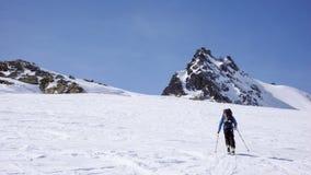 Sciatore remoto maschio che va su un pendio della neve nel remoto delle alpi svizzere durante un giro dello sci nell'inverno Immagine Stock