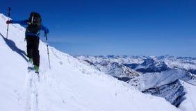 Sciatore remoto maschio che va su un pendio della neve nel remoto delle alpi svizzere durante un giro dello sci nell'inverno Fotografia Stock Libera da Diritti