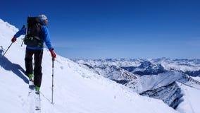 Sciatore remoto maschio che va su un pendio della neve nel remoto delle alpi svizzere durante un giro dello sci nell'inverno Immagini Stock Libere da Diritti