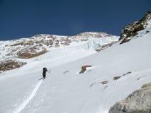 Sciatore remoto maschio durante un giro dello sci che mette le prime piste sul suo modo ad un'alta sommità alpina nelle montagne  Immagine Stock Libera da Diritti
