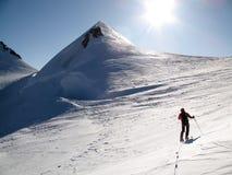 Sciatore remoto maschio su un toru dello sci sul suo modo ad un'alta sommità alpina nelle montagne di Monte Rosa su un ghiacciaio Immagini Stock