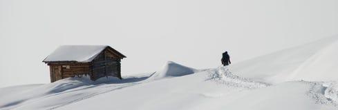 Sciatore solo che passa da un rifugio della montagna Immagini Stock Libere da Diritti