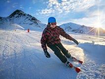 Sciatore sulla pista in alte montagne con il bello cielo il giorno soleggiato Immagini Stock Libere da Diritti