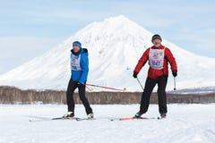 Sciatore-uomini che corrono lungo la pista dello sci di inverno su fondo del vulcano Immagini Stock