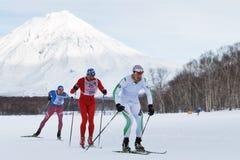 Sciatore-uomini che corrono lungo la pista dello sci di inverno su fondo del vulcano di Koryak Fotografia Stock