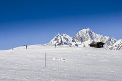 Sciatori accanto ad una cabina di legno nelle alpi italiane durante l'inverno, con lo spazio della copia Fotografia Stock Libera da Diritti