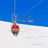 Sciatori in cappelli di Santa di Natale alla seggiovia della località di soggiorno di salute di corsa con gli sci Immagini Stock