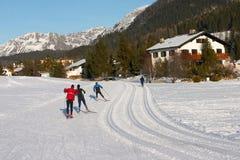Sciatori che attraversano il pæse su una pista in Davos Fotografia Stock