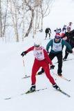 Sciatori che corrono sulla pista dello sci nella foresta di inverno Immagini Stock Libere da Diritti