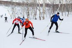 Sciatori che corrono sulla pista dello sci nella foresta di inverno Fotografie Stock